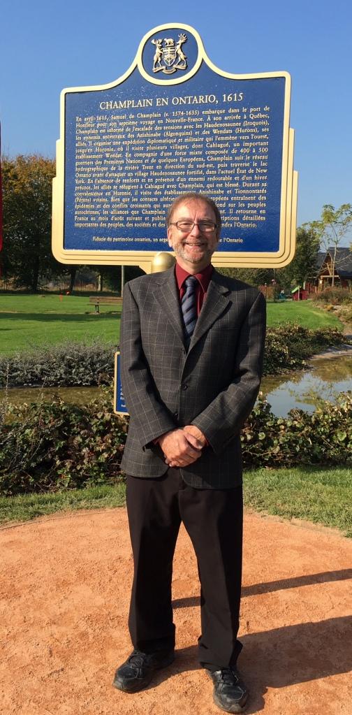 Michel Prévost, archiviste en chef de l'Université d'Ottawa, pose fièrement devant la plaque de Champlain, à Honfleur. PHOTO : Denis Vaillancourt